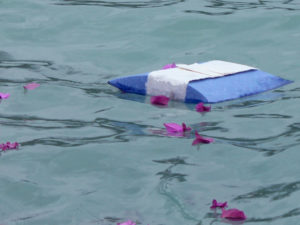 Biodegradable urn floating in water with flower petals