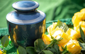 Blue and silver cremation urn with yellow roses on a green background