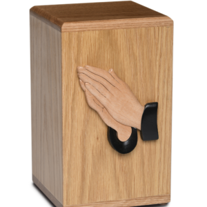 Wooden cremation urn with praying hands