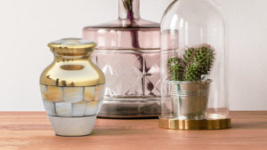 Close up of Mother of Pearl urn next to pink vase and small cactus in a dome on a wooden table